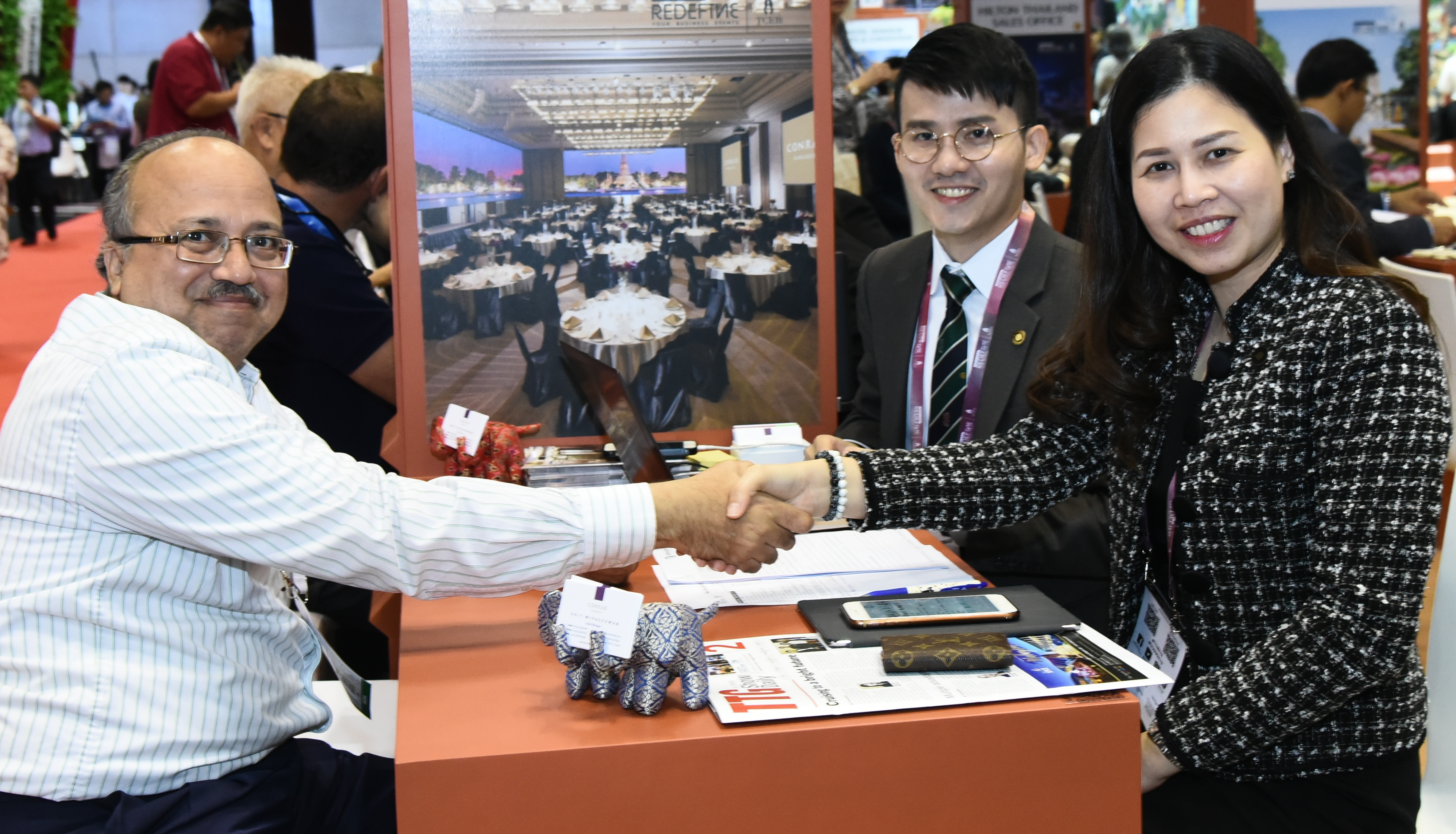 Exhibitors shaking hands with a buyer at IT&CM Asia and CTW Asia-Pacific 2019