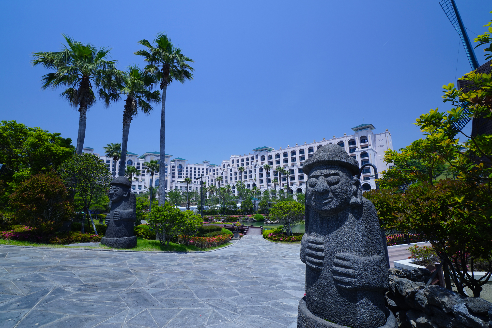 Dol Hareubang with Lotte Hotel Jeju in the background